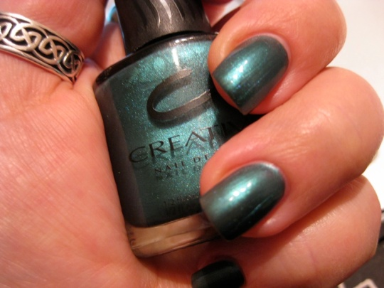 Jadegrönt nagellack i flaska och på naglar
